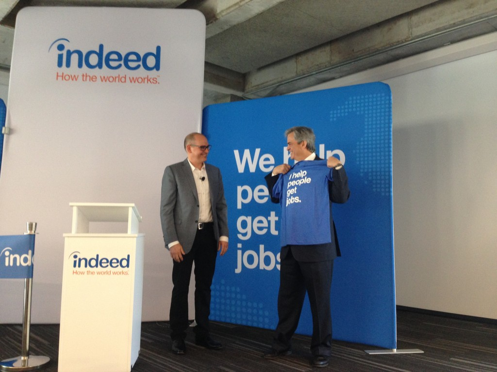 Indeed's President Chris Hyams gives Austin Mayor Steve Adler an Indeed company shirt.