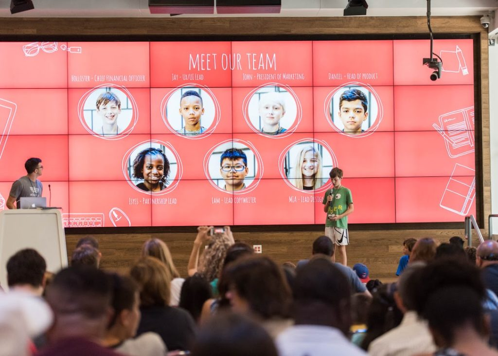 At Hello World Demo Day, a student introduces his team members.  Courtesy photo by Erika Rich.